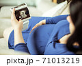 Pregnant woman holding an ultrasound picture with her baby in front of her 71013219