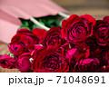 床の上の赤い薔薇の花束 71048691