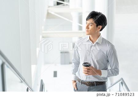 オフィスの階段で飲み物を持って立つ若い男性 71089523