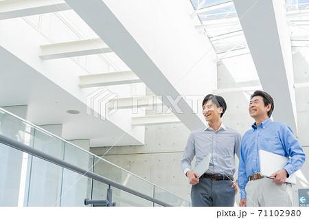 オフィスビルの中に立つ2人の笑顔の男性 71102980