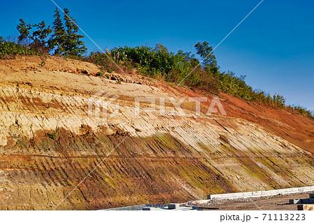 道路造成工事のために切り開かれた山の削られた斜面 71113223