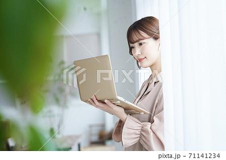 窓際でパソコンを持つビジネスウーマン 71141234