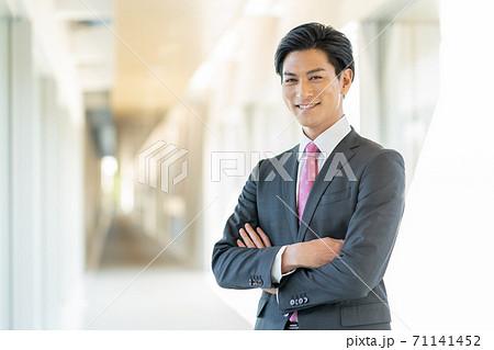 オフィスの廊下に腕組みをして立つ若い笑顔の男性 71141452