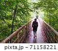 山の中の橋を渡る40代女性の後ろ姿 71158221