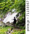 滝に近づきマイナスイオンを浴びる女性 71158567
