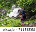 トレッキング中に森林浴と滝のマイナスイオンで癒されている女性 71158568