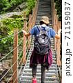 山の中のつり橋を慎重に渡る女性 71159037