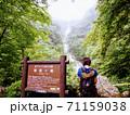 国立公園精進ケ滝の看板横で滝を見る女性 71159038