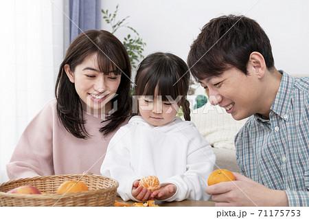みかんをむく女の子と見守る両親 若い家族イメージ 71175753