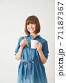 ハブラシとカップを持つ若い女性 71187367