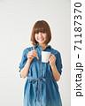 ハブラシとカップを持つ若い女性 71187370