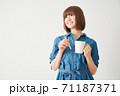 ハブラシとカップを持つ若い女性 71187371