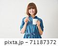 ハブラシとカップを持つ若い女性 71187372
