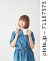 ハブラシとカップを持つ若い女性 71187373