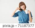 片手にコップを持ち歯を磨く若い女性 71187377