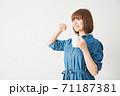 片手にコップを持ち歯を磨く若い女性 71187381