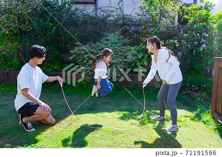 お庭で縄跳びをして遊ぶ仲良しファミリー  71191566