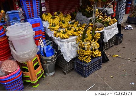 バングラデシュのダッカ 市場で販売するバナナの屋台と日用雑貨のお店 71232373