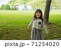 芝生の前に立つ笑顔の女の子 71254020