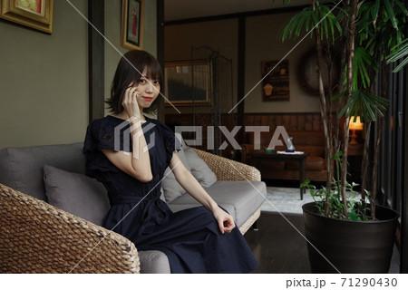 ソファに座りスマホで通話する若い女性 71290430