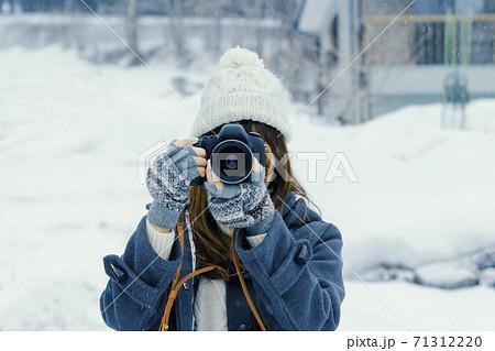 雪の中カメラを構えて撮影する女性 71312220