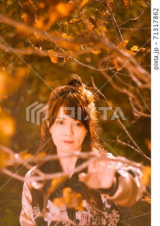 紅葉した木の枝を額縁にしてポートレート 71317862