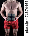 Sexy surprise concept. Macho muscular torso posing with gift box. Santa claus for adult girls.  71370465
