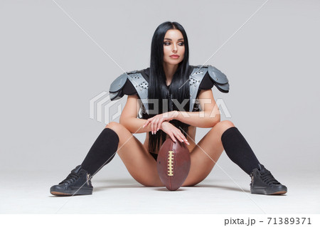 Beautiful sporty brunette dressed in bikini and American football uniforms posing sitting on the floor with a ball between her legs isolated on grey background 71389371