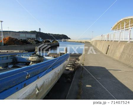 漁港の灯台に続く防波堤の入り口辺りに船のある風景 71407524