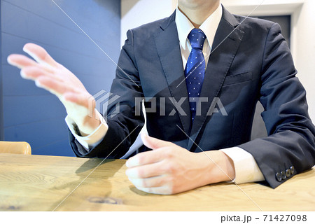 商談締結のためお客様に説明をし、片手が出るサラリーマン 71427098