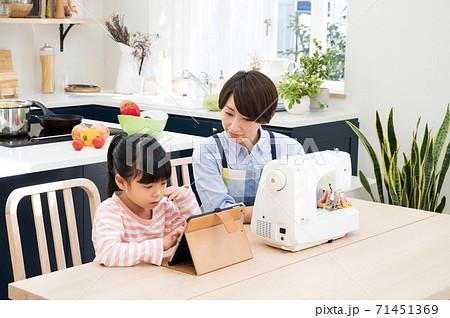 ミシンで裁縫しながら子供も学習を見守る母親 71451369
