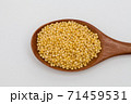 Wooden spoon with millet on white 71459531