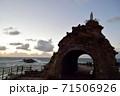 夕暮れ時の聖母の岩と岩の向こうに見える観光客の姿 71506926