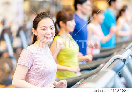 ジムで走る若い人々  71524082