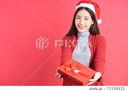 Beautiful Asian woman holding red gift box on red background 71539325