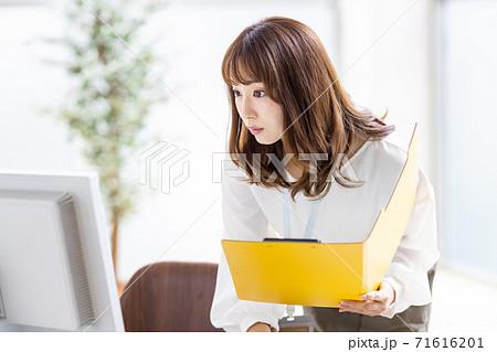 中腰でデスクトップモニターを覗き込むビジネスウーマン 71616201