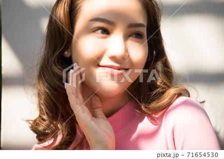 外に建物の影に立っている美人女性の顔写真 71654530