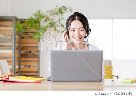 リビングでウェブ会議する若い女性 71665249