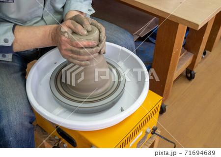 指を折り曲げて指先で粘土の真ん中を真下に押して穴を開けて粘土の量を決める作業 71694689
