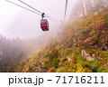 三重県菰野町 紅葉の御在所岳 霧の山を登っていく御在所ロープウエイの赤いゴンドラ 71716211