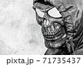 Stylized image of death on a concrete wall. A close-up of a skull in a hood is depicted on a white wall 71735437