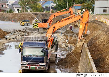 水路工事現場でのパワーショベルによる土砂のダンプカーへの積み上げ 71737452