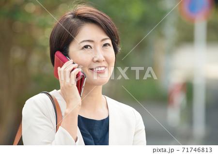 スーツを着てスマホで通話する日本人ビジネスウーマン・働く40代の女性 71746813