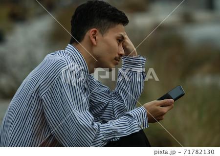 スマートフォンを持ち落ち込む男性 71782130