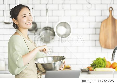 パソコンを見ながら料理を作る女性 71784725