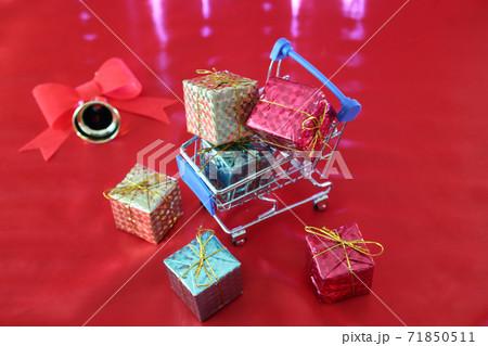 赤い布に置いたクリスマスプレゼントとミニチュアのショッピングカート 71850511
