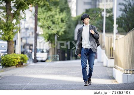 バックパックを持って歩道を歩く若い男性 71862408