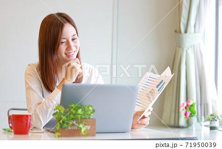 あごに手を当て笑顔でPCを見る女性 71950039
