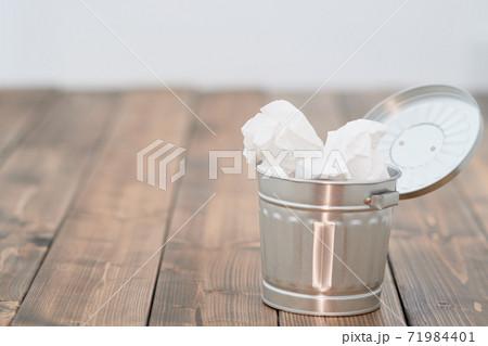 ブリキのごみ箱と紙ごみ_木目背景 71984401