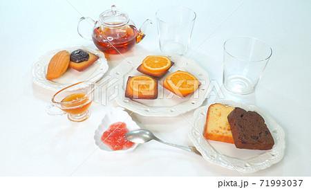 たくさんのマドレーヌやパウンドケーキでお茶をする様子 71993037